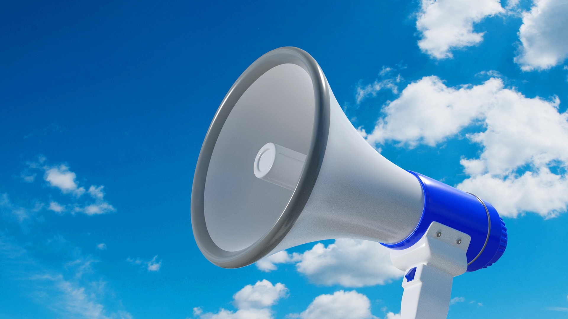 Photo of white megaphone with blue sky and clouds in the background