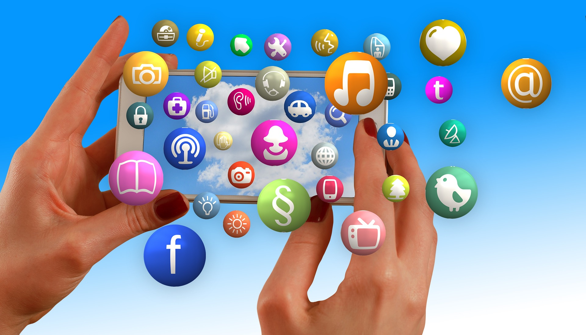 Abstract image of lady's hands holding smartphone with social media icons flying out the screen.